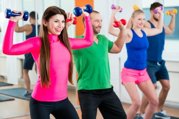 Grupo de atletas en gimnasia haciendo gimnasia con pesas.