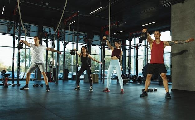 Un grupo de atletas musculosos haciendo ejercicio en el gimnasio.