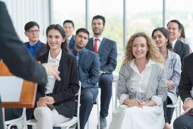 Grupo de audiencia diversa escuchando al entrenador de negocios en la reunión de negocios y seminario de capacitación para el éxito laboral