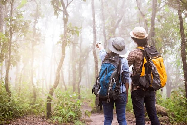 Grupo de aventuras asiáticas de amigos sonrientes caminando con mochilas.