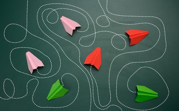 Grupo de aviones de papel con largos caminos enredados sobre un fondo verde. concepto de un líder fuerte con pensamiento extraordinario, toma de decisiones rápida. encontrar la solución óptima y sencilla en los negocios