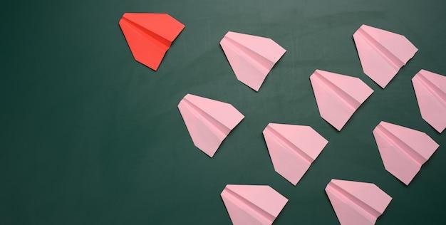 Un grupo de aviones de papel rosa sigue al primer avión rojo.