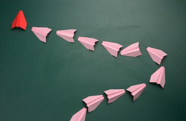 Grupo de aviones de papel rosa siguiendo el primer rojo sobre una superficie verde. el concepto de unir un equipo para lograr metas, un líder fuerte, un grupo altamente efectivo, coordinación de acciones.