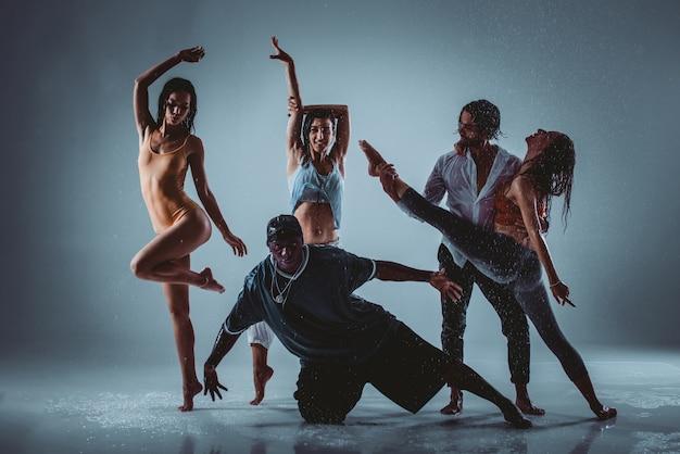 Grupo de bailarines bailando en el escenario con efecto lluvia