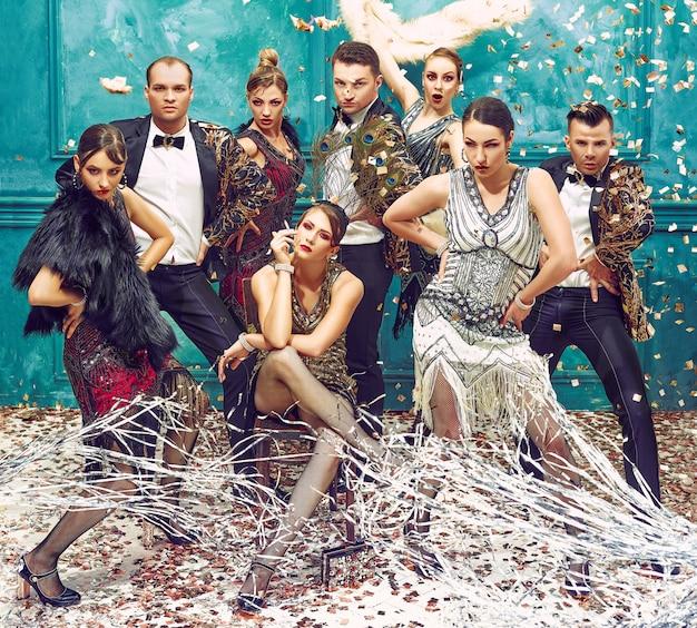 Grupo de bailarines retro con confeti dorado