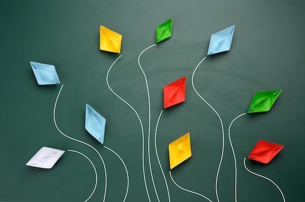 Grupo de barcos de papel multicolores vuela en diferentes direcciones sobre una superficie verde, vista superior. gestión ineficaz, desunión del equipo, opiniones divergentes