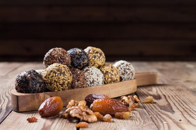 Un grupo de bolas de energía acostado en una bandeja de madera con un mango. mesa de madera borrosa. comida natural orgánica.