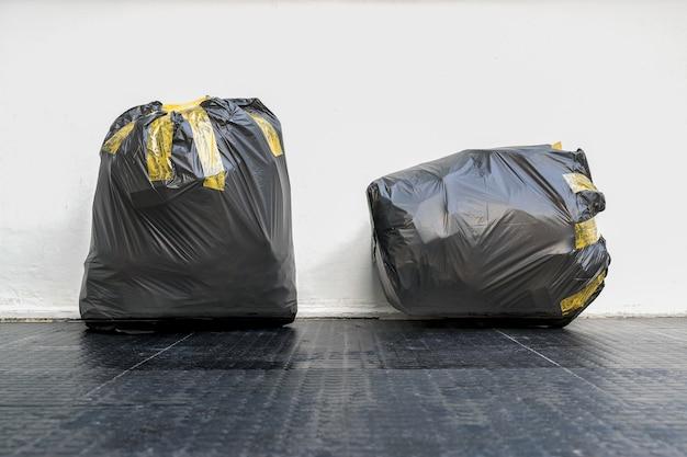 Grupo de bolsas de basura negras completamente cubiertas con cinta adhesiva.