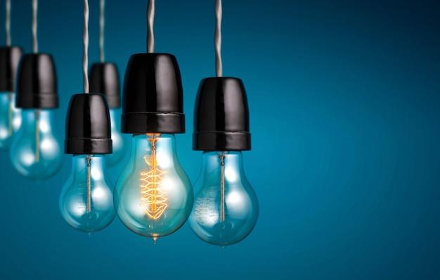 Grupo de bombillas vintage con una bombilla antigua encendida, idea creativa y liderazgo.
