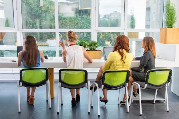 Grupo de bonita empresaria trabajando junto con nuevo proyecto de inicio utilizando la computadora portátil en loft moderno