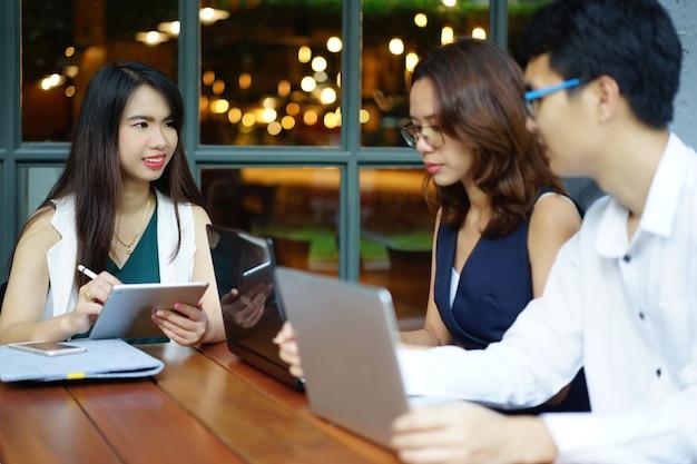 Grupo borroso de empleado asiático trabajando y reunión en concepto de sala de oficina