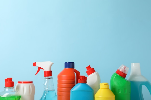 Grupo de botellas con detergente sobre fondo azul, espacio para texto