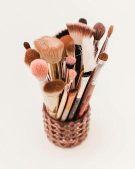 Grupo de brochas de maquillaje dentro de un jarrón