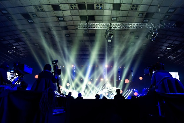 Un grupo de camarógrafos trabajando durante el concierto. evento de transmisión televisiva. siluetas de trabajadores en el contexto de vigas de colores.