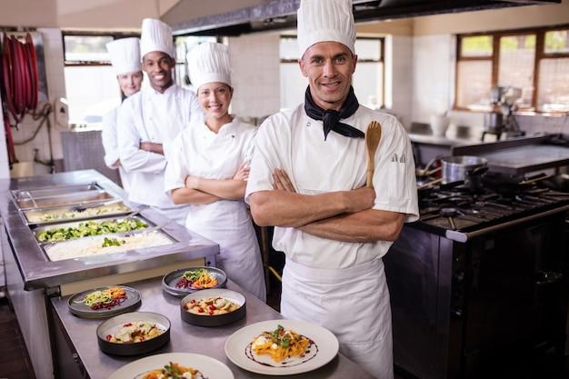 Grupo de chefs de pie con los brazos cruzados en la cocina