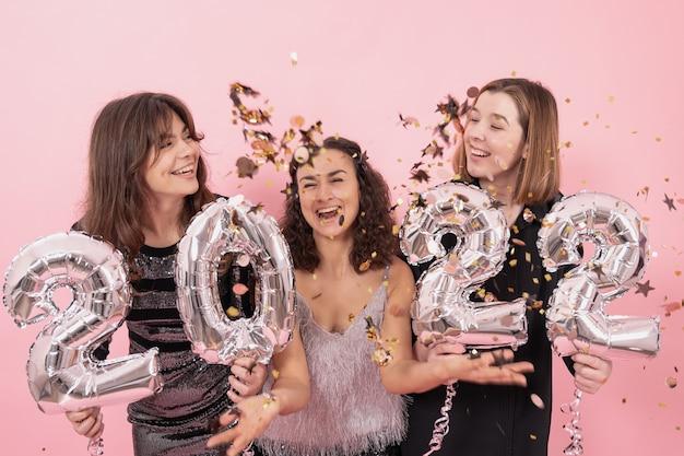 Un grupo de chicas alegres con globos plateados en forma de números.