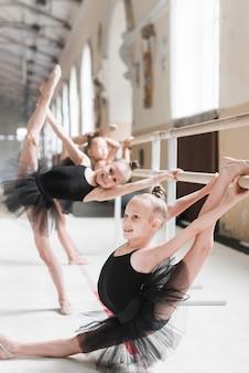 Grupo de chicas de ballet practicando con la ayuda de barre