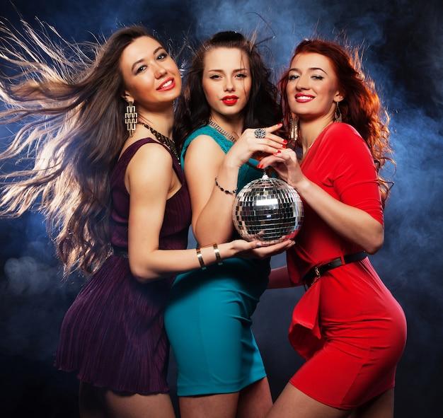 Grupo de chicas de fiesta con bola de discoteca