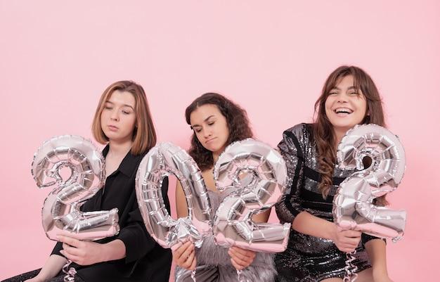 Un grupo de chicas con globos plateados en forma de números.