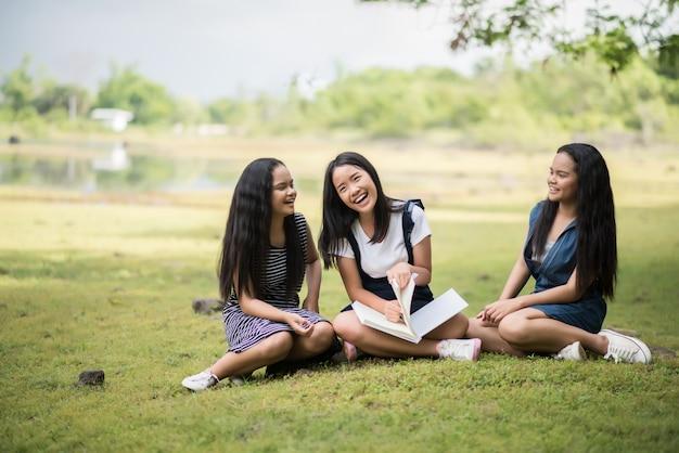 Grupo de chicas hermosas estudiantes se preparan para el examen en el parque
