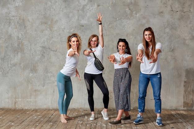 Grupo de chicas jóvenes están posando contra la pared sonriendo y mostrando gestos con sus manos