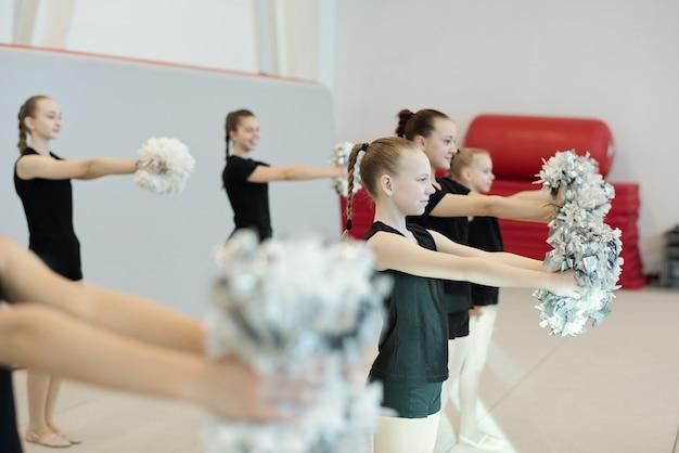 Grupo de chicas porristas en ropa negra bailando con pompones mientras se prepara para la competencia