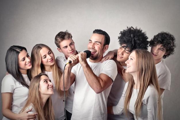 Grupo de chicas viendo a un hombre cantando.
