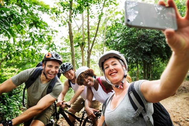Grupo de ciclistas diversos en el bosque.