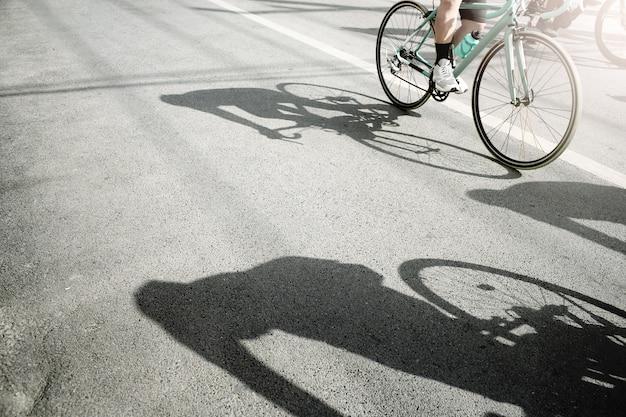 Grupo de ciclistas pedaleando en una bicicleta de carreras con sombra dura en un día soleado.