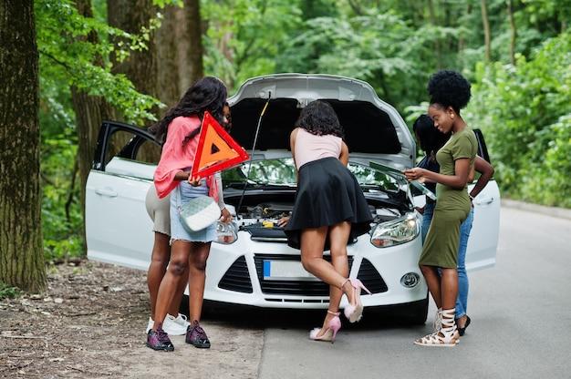 Grupo de cinco mujeres viajeras mirando el capó abierto del coche roto