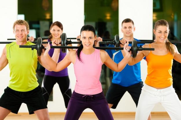 Grupo de cinco personas que hacen ejercicio con pesas en el gimnasio o en el gimnasio para ganar fuerza