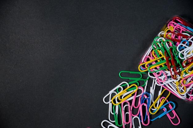 Grupo de clips de papel de colores junto con sus cajas sobre un fondo negro espacio negro para texto