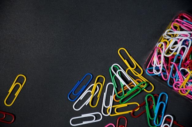 Grupo de clips de papel de colores sobre fondo negro espacio negro para el texto