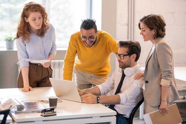 Grupo de colegas multiétnicos jóvenes creativos discutiendo el diseño del proyecto mostrado por el diseñador web en la oficina