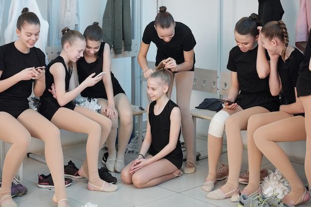 Grupo de colegialas que se preparan para el entrenamiento de porristas en el vestuario: niñas que usan teléfonos inteligentes para navegar por la red mientras una chica morena hace cola de caballo a un amigo