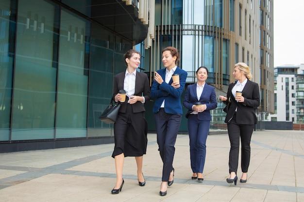 Grupo de compañeras de trabajo caminando con café para llevar al aire libre, hablando, sonriendo. vista frontal de cuerpo entero. concepto de descanso laboral