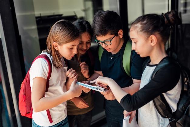 Grupo de compañeros discutiendo sobre la tarea frente a la escuela