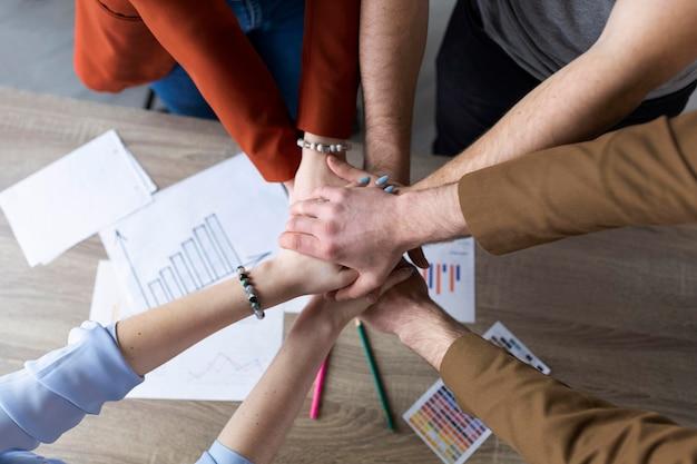 Grupo de compañeros de trabajo juntando sus manos