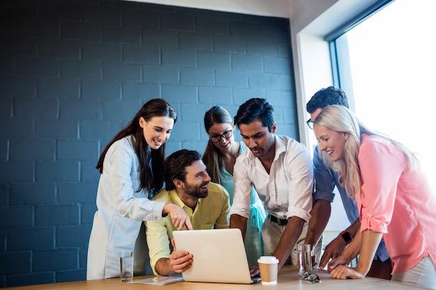 Grupo de compañeros de trabajo mirando una computadora portátil