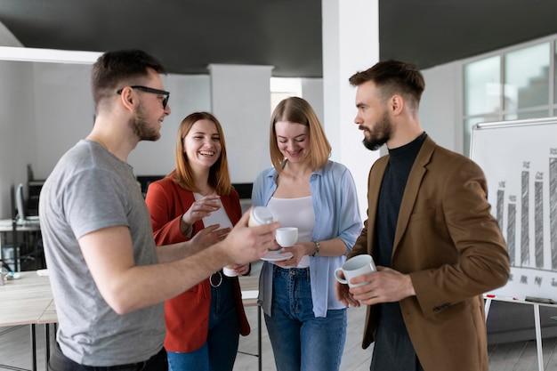Grupo de compañeros de trabajo en la oficina hablando