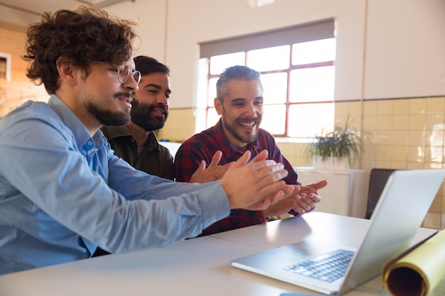 Grupo de compañeros de trabajo viendo capacitación en línea o seminario web