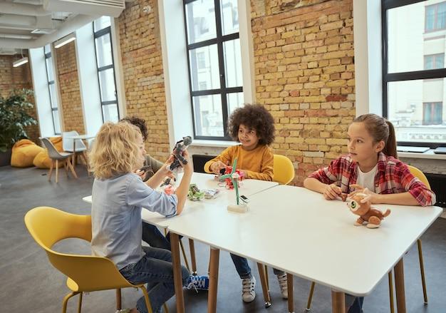 Grupo de comunicación de niños pequeños inteligentes que construyen juguetes técnicos y hacen robots mientras