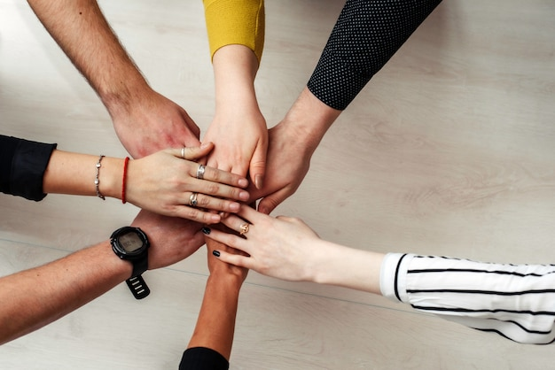 Grupo de concepto multiétnico diverso del trabajo en equipo de la gente. concepto de colaboración de trabajo en equipo. manos de oficinistas en un círculo
