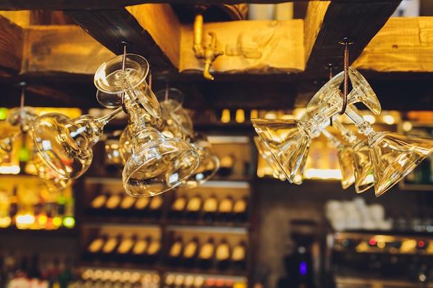 Grupo de copas de vino vacías colgando de vigas de metal en un bar.