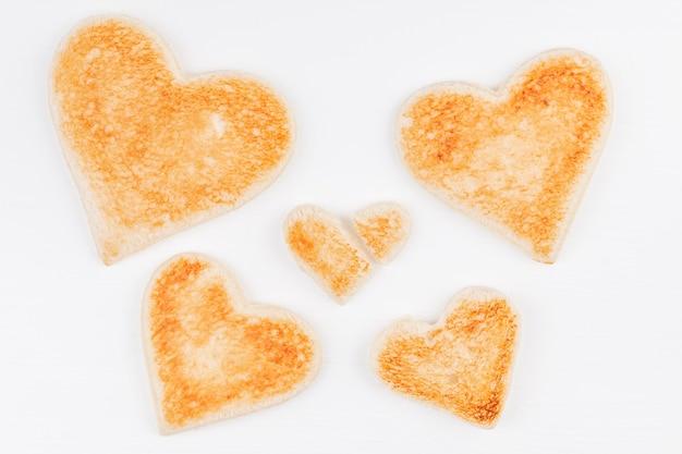 Grupo de corazones de pan tostado con un corazón roto juntos sobre fondo blanco.