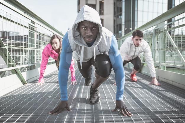 Grupo de corredores urbanos preparándose en la línea de salida