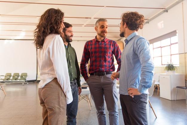 Grupo creativo discutiendo ideas, de pie en círculo