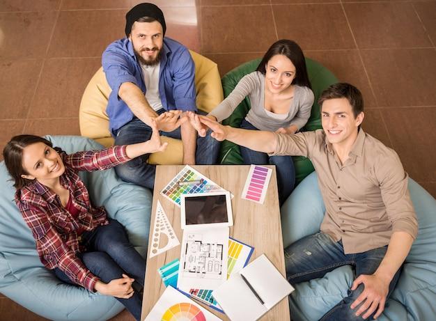 Grupo creativo de diseñadores juntando las manos.