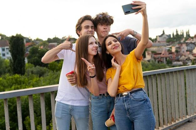 Grupo de cuatro amigos pasando tiempo juntos al aire libre y tomando selfie