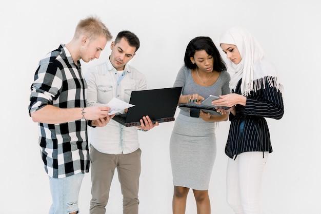 Grupo de cuatro estudiantes multiétnicos, trabajando estudiando juntos, usando una computadora portátil y una tableta, de pie sobre fondo blanco.